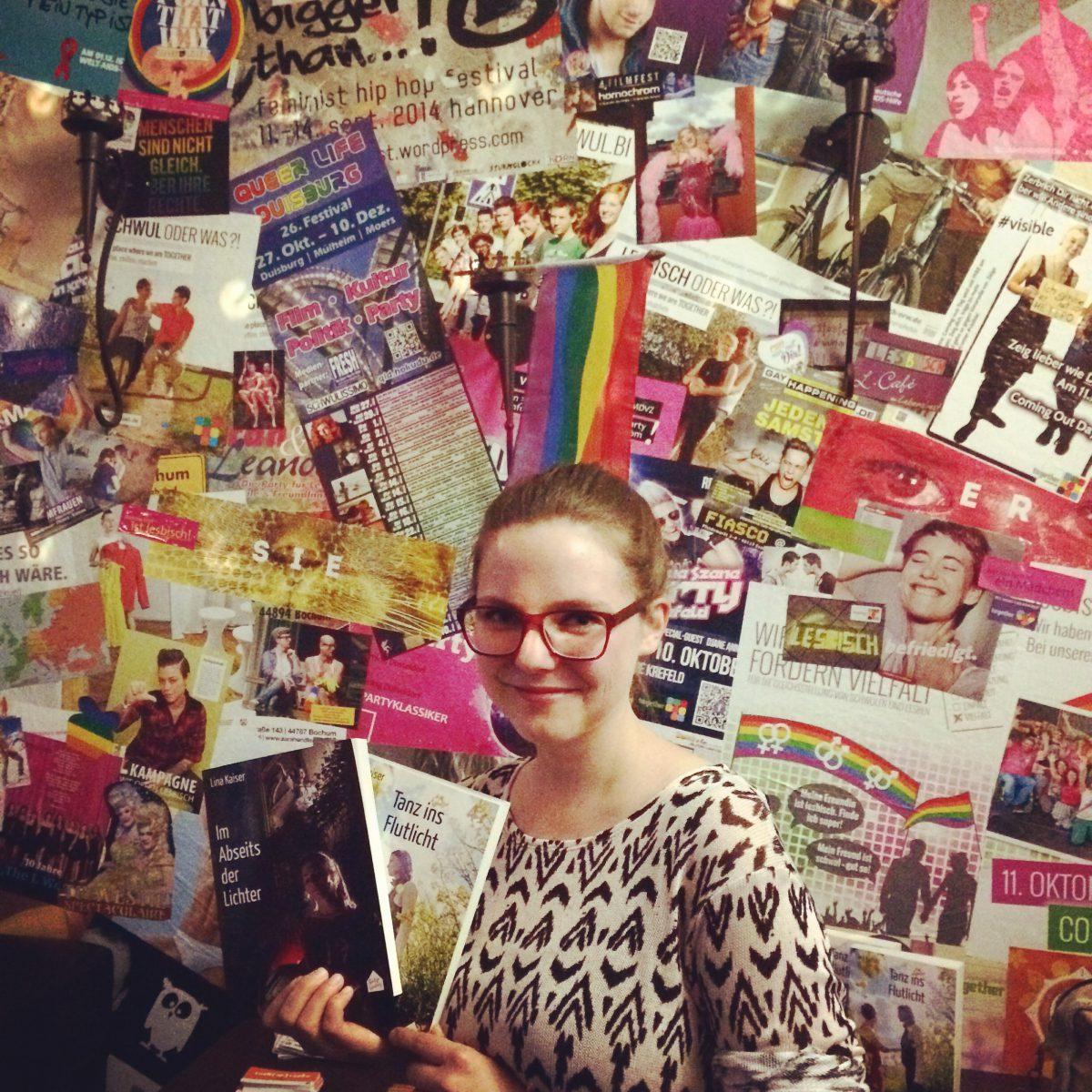 Lina Kaiser bei einer Lesung im together Mülheim vor einer LGBT-Bilderwand