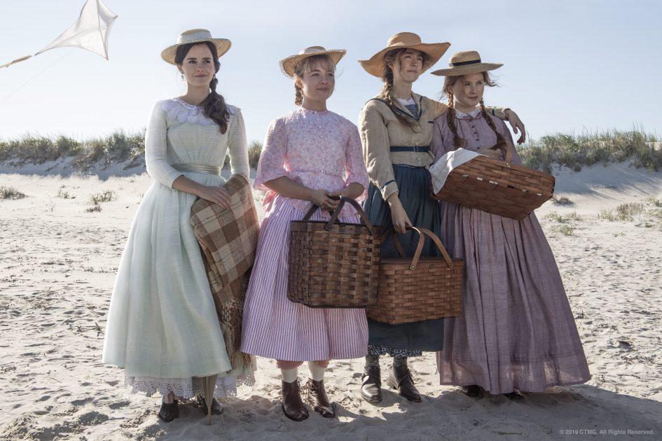 Vier junge Frauen im 19. Jahrhundert stehen am Strand und schauen in die Ferne.
