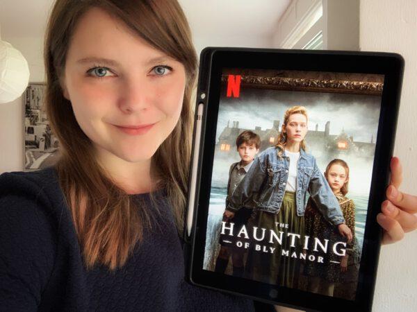 """Foto: Frau hält Tablet, auf dem die Serie """"Spuk in Bly Manor"""" angezeigt wird."""